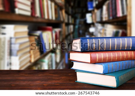 Stack of books on table on bookshelves background - stock photo