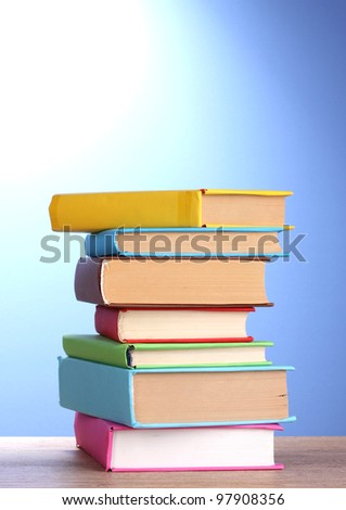 Stack of books on wooden table on blue background - stock photo