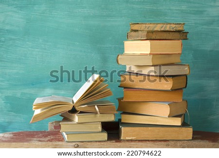 stack of books, one open, grungy background,free copy space  - stock photo