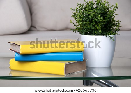stack of books placed on glass table in living room - stock photo