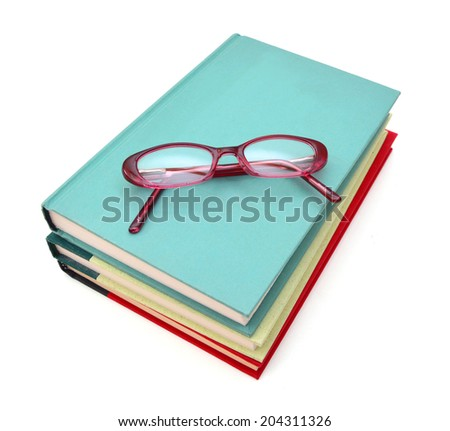 stack of books with a pair of eyeglasses on top  - stock photo