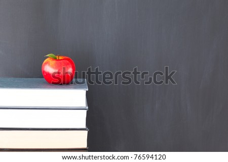 Stack of books with a red apple and a clean blackboard - stock photo