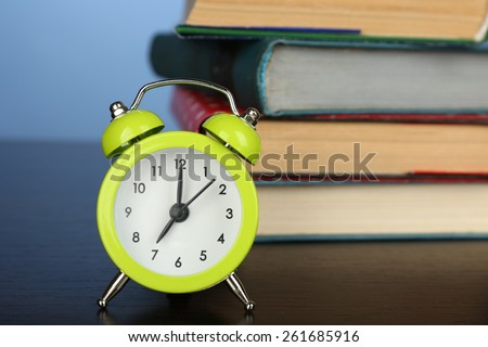 Stack of books with alarm clock on wooden desk and colorful background - stock photo
