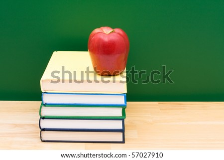 Stack of  books with an apple in front of the chalkboard, School Days - stock photo