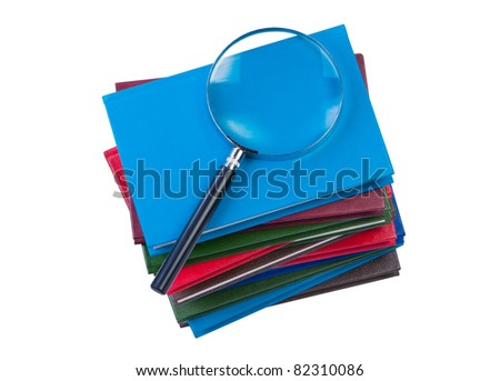 Stack of books with magnifying glass isolate on white background. Clipping paths. - stock photo