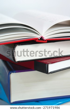 Stack of books with open book on top - stock photo