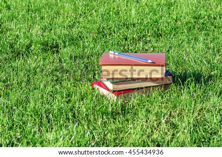 stack of books with pencil on green grass in the park - stock photo