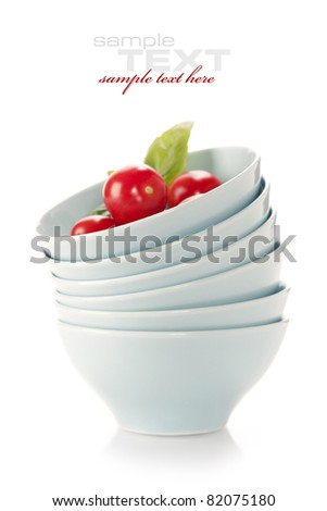 Stack of bowls and fresh tomatoes over white (with sample text) - stock photo