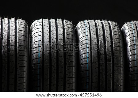 Stack of brand new high performance car tires on clean low-key black studio background - stock photo