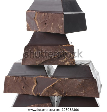 Stack of broken dark chocolate pieces close-up on white background. - stock photo