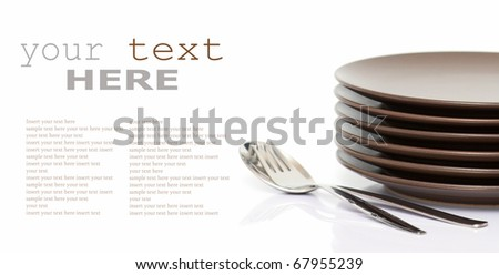 Stack of brown round plates with spoon and fork (with sample text) - stock photo