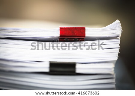 Stack of business report paper files with red and black clips - stock photo