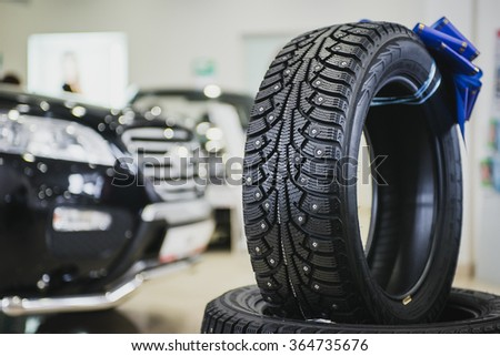 Stack of car tires in the showroom. New cars in bokeh - stock photo