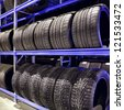 Stack of car tires on warehouse closeup - stock photo