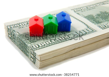 Stack of cash with models of houses in a row - stock photo