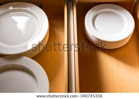 Stack of ceramic white plates in side a wooden cabinet drawer. - stock photo