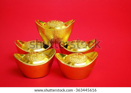 Stack of Chinese Gold Ingots on red Background. - stock photo