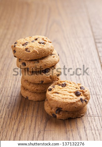 stack of chocolate biscuits with chocolate on wooden table - stock photo