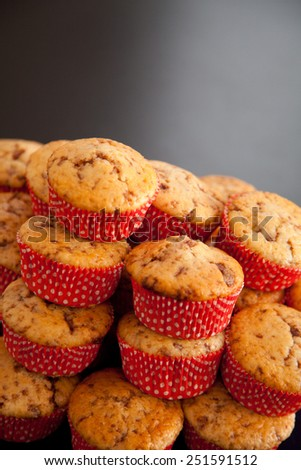 stack of chocolate chip muffins in red, white dotted shapes - stock photo