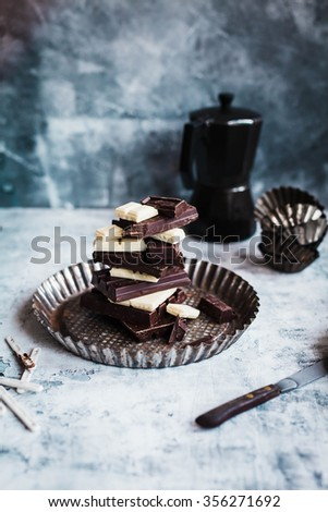 Stack of chocolate sliced. White, dark, milk chocolate on a cooking sheet over stone table. vertical rustic image. Copy space.  - stock photo