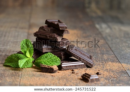 Stack of chocolate slices with mint leaf on a wooden table. - stock photo