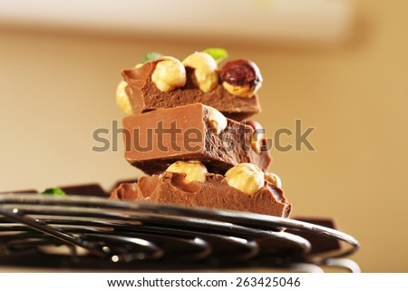 Stack of chocolate with nuts on light background - stock photo