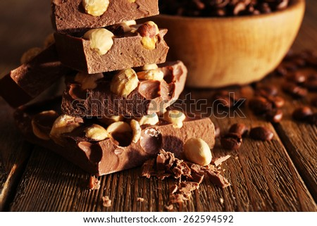Stack of chocolate with nuts on wooden table, closeup - stock photo