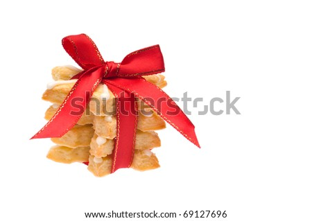 Stack of Christmas cookies wrapped in red ribbon over white