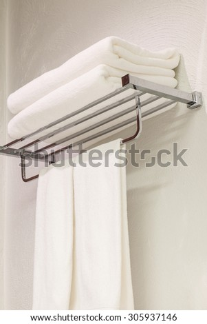 Stack of clean white towels on stainless steel rack in restroom for shower background - stock photo