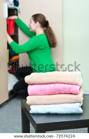 Stack of clothes and young caucasian woman arranging things in the wardrobe on background. - stock photo