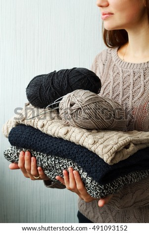 Stack of clothes from knitted knitwear in woman's hands