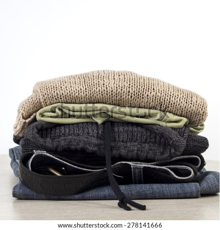 Stack of clothes on a Wooden table  in front of the white wall. - stock photo