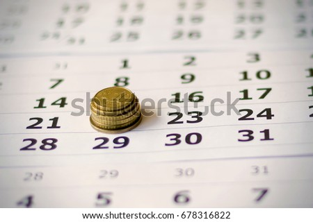 Stack of coins on a calendar sheet