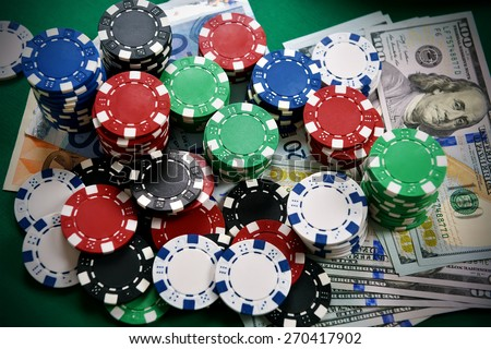 Stack of color poker chips and money - stock photo