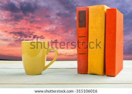 Stack of colorful books and cup on wooden table on natural blurred background. Back to school. Copy space - stock photo