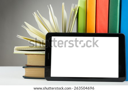 Stack of colorful books and electronic book reader. Electronic library concept. Back to school. Copy space - stock photo