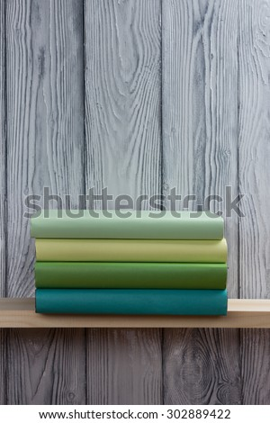Stack of colorful books and green apple on wooden shelf. Back to school. Copy space - stock photo