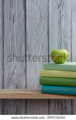 Stack of colorful books and green apple on wooden shelf. Back to school. Copy space