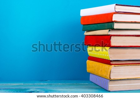 Stack of colorful books, grungy blue background, free copy space Vintage old hardback books on wooden shelf on the deck table, no labels, blank spine. Back to school. Education background - stock photo