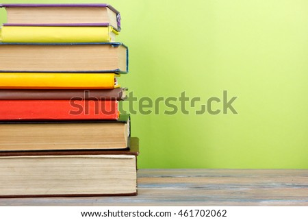 Stack of colorful books, grungy green background, free copy space Vintage old hardback books on wooden shelf on the deck table, no labels, blank spine. Back to school. Education background