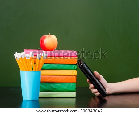 Stack of colorful books with electronic book reader near empty green chalkboard. Sample for text - stock photo