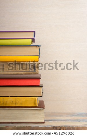 Stack of colorful books, wooden beige background, free copy space Vintage old hardback books on wooden shelf on the deck table, no labels, blank spine. Back to school. Education background - stock photo