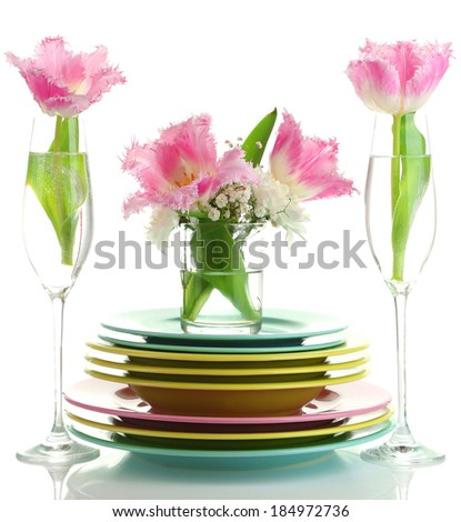 Stack of colorful ceramic dishes and flowers, isolated on white - stock photo
