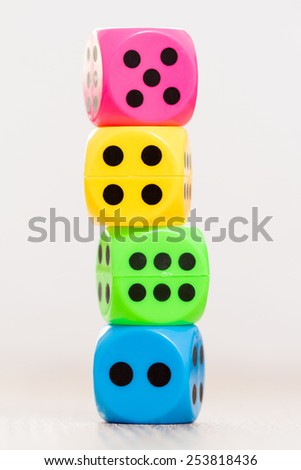 Stack of colorful dice, isolated on blurry background