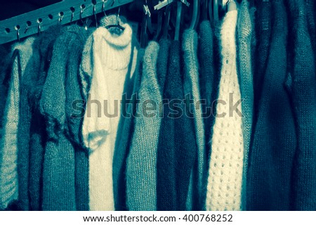 Stack of colorful  knitted colorful clothes - sweaters, dresses, cardigans etc. Toned monochrome photo. - stock photo