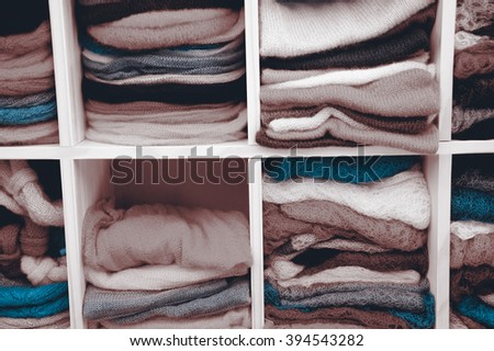 Stack of colorful  knitted colorful clothes - sweaters, dresses, cardigans etc.Toned photo. - stock photo