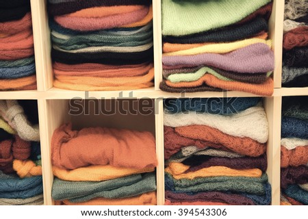Stack of colorful  knitted colorful clothes - sweaters, dresses, cardigans etc.Toned photo  - stock photo