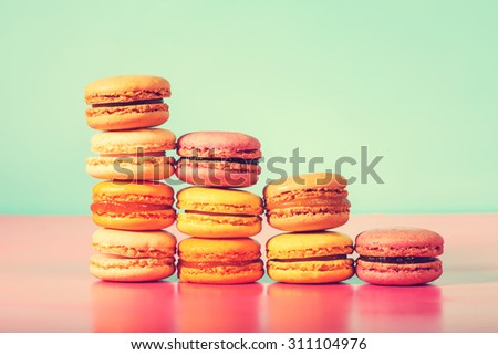 Stack of colorful macarons on a bright pastel background in vintage style - stock photo
