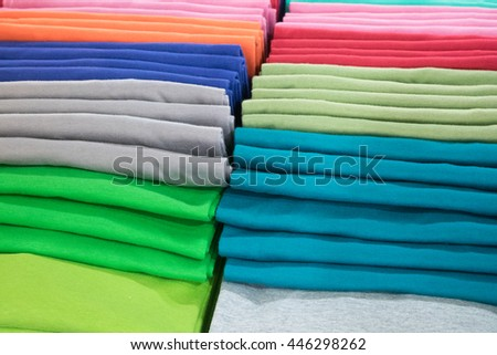 Stack of colorful shirts folded neatly ant arranged for sale - stock photo