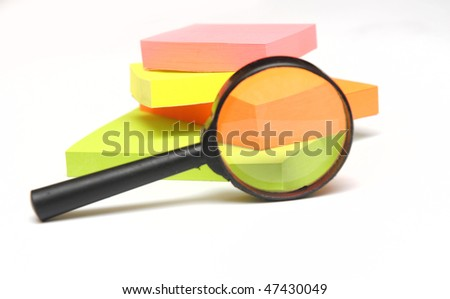 stack of colorful sticks and  magnifying glass isolated